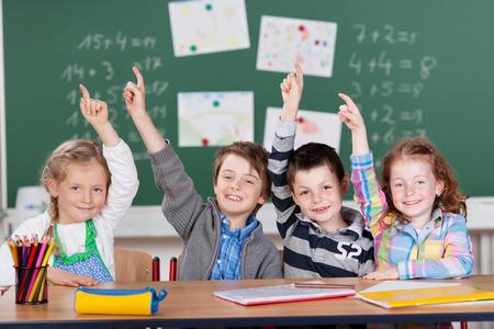 4 少し学童が興奮して式で手を上げて質問、2 人の女の子および行内の机に座っている 2 人の男の子への答えを知っているを表示するには 写真素材