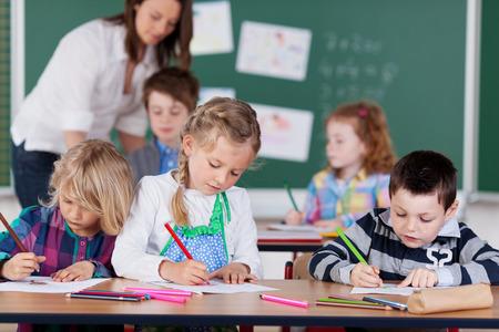salon de clases: Grupo de ni�os jovenes que estudian en la escuela jard�n de ni�os, con especial atenci�n a un ni�o y dos ni�as de dibujo con l�pices de colores de l�piz en la parte delantera como el maestro trabaja con los alumnos en la parte posterior