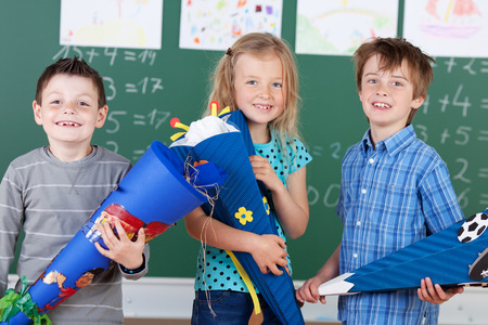 The first day at school - three happy young children, two boys and a girl, pose in front of the blackboard with colorful gift wrapped cones in their hands and proud happy smiles Standard-Bild