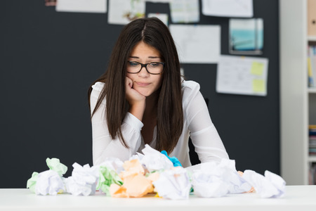 come up: Frustrated young businesswoman with a huge pile of crumpled paper on her desk grimacing as she fails to come up with a solution or creative idea