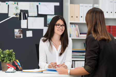 talking: Two young businesswomen having a meeting in the office sitting at a desk having a discussion with focus to a young woman wearing glasses Stock Photo