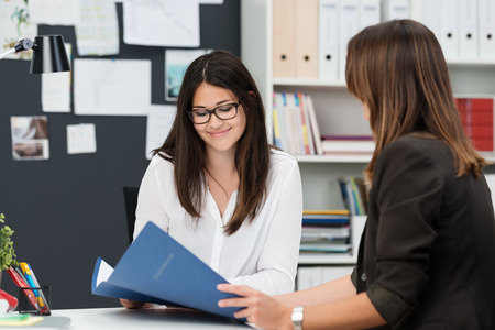 Two young work colleagues discussing some paperwork as they sit together at a desk in the office with focus to a smiling young woman in glasses 写真素材