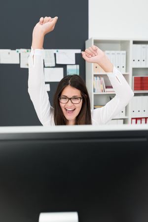jubilation: Excited Businesswoman at Desk Celebrating with Arms in Air