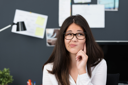 come up: Thoughtful young businesswoman grimacing as she sits at her desk pondering a major problem unable to come up with an answer Stock Photo
