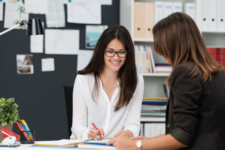 education help: Attractive businesswoman in a meeting in the office with a female colleague smiling as she writes something in a file Stock Photo