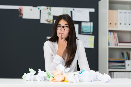 pondering: Young woman with writers block sitting in an office with a desk littered with crumpled paper as she sits looking thoughtfully into the air with her finger to her chin seeking new ideas