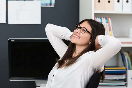 student studying: Happy successful young businesswoman wearing glasses relaxing at work leaning back in her chair with a smile of satisfaction and hands clasped behind her head Stock Photo