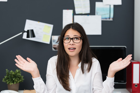 Young businesswoman showing her ignorance at the office shrugging her shoulders with a look of frustration photo