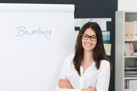 Smiling confident young businesswoman doing a presentation standing alongside a flip chart in the office with folded arms photo