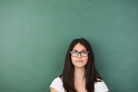 seeks: Thoughtful young woman wearing glasses standing staring up into the air as she seeks a solution while standing in front of a blank chalkboard with copyspace Stock Photo