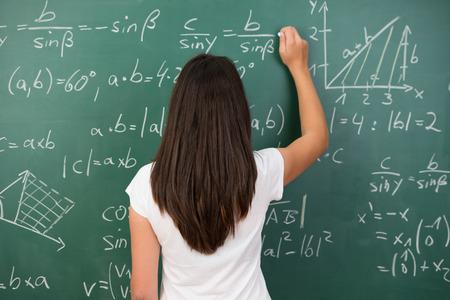 křída: Clever mladá žena řešení matematického problému stojící zády ke psaní fotoaparátu na vysoké škole tabuli