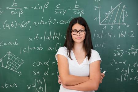 Intelligente junge weibliche Mathematik Schüler oder Lehrer mit Brille steht vor einer Tafel mit mathematischen Gleichungen mit verschränkten Armen und einem Stück Kreide in der Hand