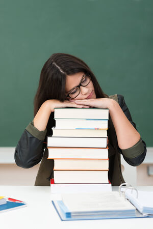 Exhausted young female student sleeping at her desk in class resting her head on a high stack of textbooks photo