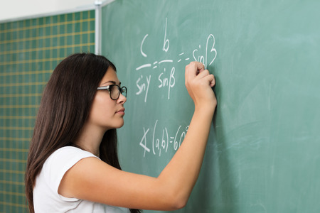 Young female teacher or student wearing glasses standing at the blackboard doing mathematics equations and problems during class in college or university