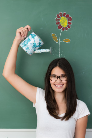 ion: Smiling student watering a colorful flower on her head drawn ion the chalkboard behind in a fun conceptual image Stock Photo