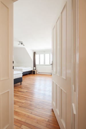double beds: View through the door past white paneling into a spacious airy loft bedroom with two double beds, windows and a wooden parquet floor Stock Photo