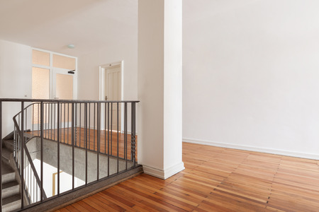 clean house: Wooden landing a flight of interior stairs in a fresh white painted building interior with a simple metal railing Stock Photo