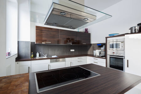 electrical appliances: Interior of a modern fitted kitchen with built in electrical appliances, wooden cabinets and a recessed counter