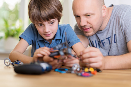 lean over: Father helping his young son build a model toy as they lean over a table together peering at the pieces