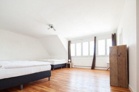 double beds: Bright white loft bedroom interior with a row of small windows and two double beds on a wooden parquet floor Stock Photo