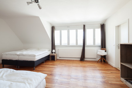 double beds: Large white painted bedroom interior with a wooden parquet floor two double beds and a shelving units in minimalist style