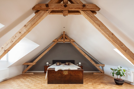 roof apartment: Interior of a loft or dormer bedroom in the apex of a roof with visible timber roof trusses , a patterned parquet floor and double bed