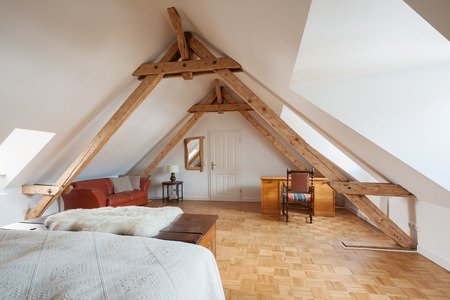 roof light: Spacious loft bedroom interior in a roof apex viewed from the bed showing exposed roof timbers, a wooden parquet floor and desk