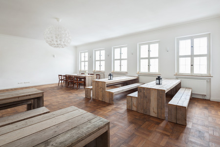 Empty simple rustic wooden benches and tables in a bright white commercial canteen interior with a parquet floor and row of windows
