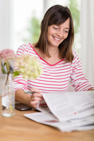 Attractive young woman smiling as she reads good news in the newspaper while having a relaxing morning at home sitting at the table photo