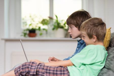 hermanos jugando: Dos niños pequeños, o hermanos, sentado en un sofá de juego en un equipo portátil, vista lateral delante de una ventana Foto de archivo
