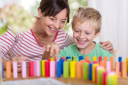 domiciles: Happy smiling young boy playing with colorful building blocks helped by his loving mother with her arm around his shoulders Stock Photo
