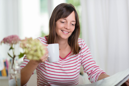browses: Attractive woman enjoying a mug of coffee in the morning as she browses the newspaper smiling with enjoyment and pleasure Stock Photo