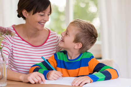 Loving little boy smiling at his mother as she sits at the table with him at home helping him with his school work Standard-Bild