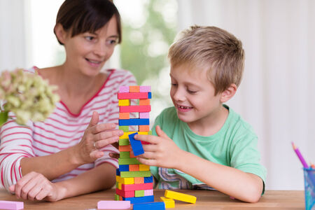 Young mother helping her small son build a tower from colorful building blocks as they sit together at the dining table at home photo