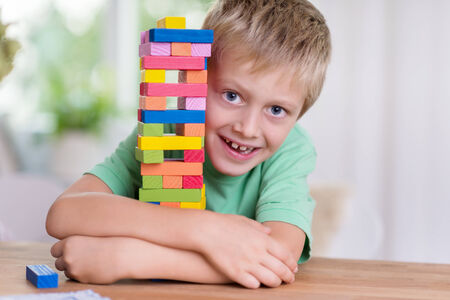 hugh: Cute happy little boy hugging a colorful tower on the dining table that he has just built from building blocks peering around the side at the camera with a cheeky grin