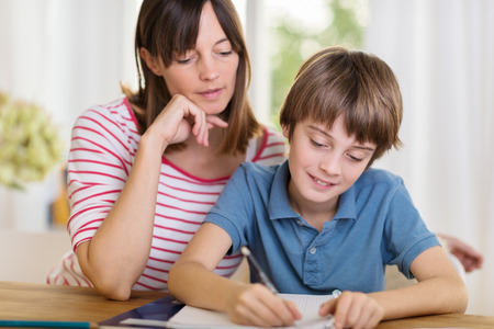 Young mother sitting at a table at home helping her small son with his homework from school as he writes notes in a notebook photo