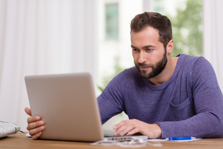 Attractive bearded man in casual clothes sitting at a table working on his laptop computer at home in front of a window photo