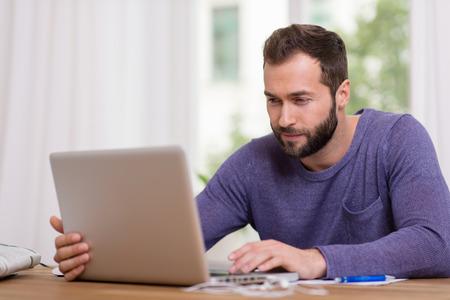 ropa casual: Hombre barbudo atractivo en ropa casual sentado en una mesa de trabajo en su ordenador port�til en casa delante de una ventana