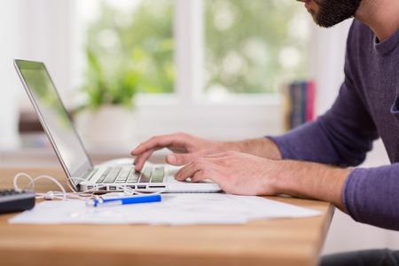 computadora: Cierre de vista de ángulo bajo de un hombre que trabaja desde su casa en un ordenador portátil sentado en un escritorio, navegar por internet