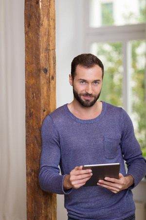 Smiling relaxed bearded man in a casual t-shirt leaning against an old wooden door jamb holding a tablet computer in his hands and smiling at the camera