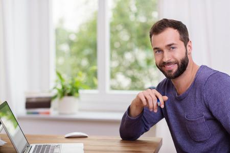 ハンサムなあごひげを生やした彼のラップトップ コンピューターの回転テーブルに座ってホーム オフィスでカメラに笑顔を 写真素材