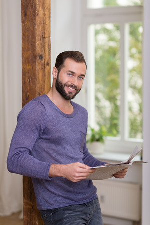 Friendly bearded man relaxing with a newspaper leaning against a vintage wooden door jamb looking at the camera with a happy smile