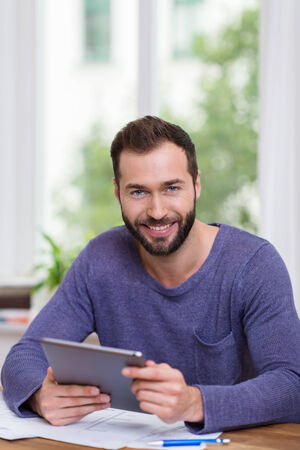 Smiling happy man working with a handheld tablet computer at his desk in front of a window