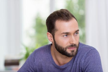 hombre con barba: Hombre con barba pensativo mirando a la derecha del marco con una expresión lejana soñadora como él recuerda el pasado o hace planes para el futuro Foto de archivo
