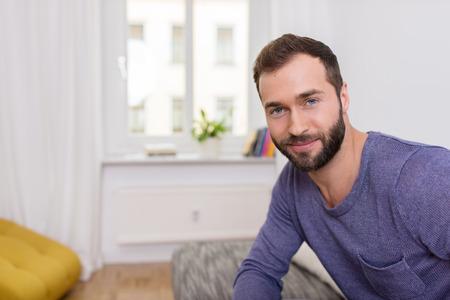 カメラを見て彼のアパートでソファーに座っていたフレンドリーな笑顔と魅力的なひげを生やした男