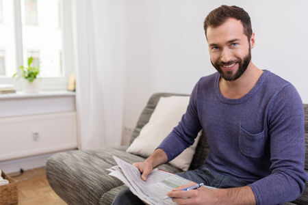 Smiling Middle Age Man Sitting on Couch Holding Newspaper and Pen. Looking at Camera.
