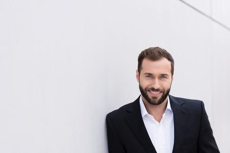 beau mec: Sourire Good Looking Moyen Age homme en costume noir et blanc Se appuyant sur mur blanc. Banque d'images