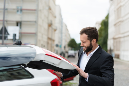 Businessman closing the boot of his car as he retrieves his belongings before leaving it in the parking lot