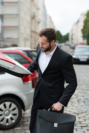 car parking: Smiling businessman getting his briefcase from the boot of his car as he arrives at work in the morning Stock Photo