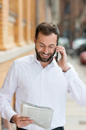 shirtsleeves: Smiling businessman in his shirtsleeves chatting on his mobile as he walks along an urban street with a magazine in his hand Stock Photo